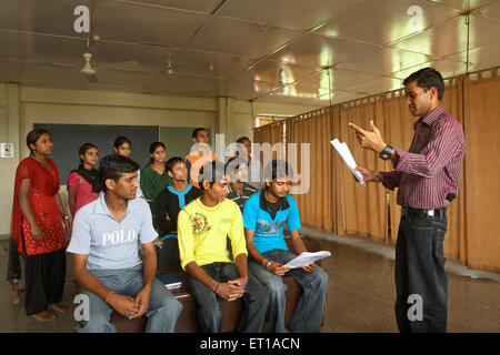 Volunteer conducting spoken English class for rural youth socio economic initiative started by NGO Chinmaya Organization - Stock Photo
