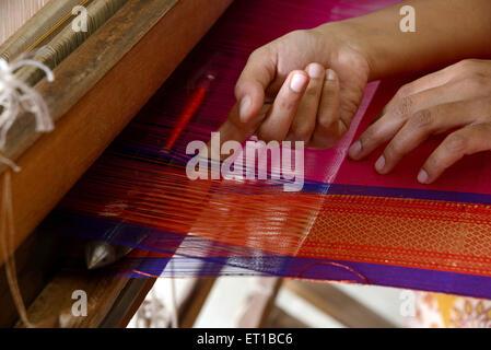 Woman weaving saree on handloom Maharashtra India Asia - Stock Photo