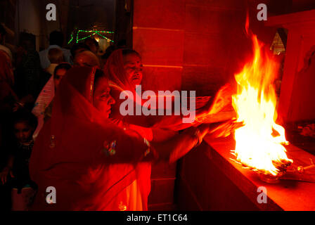 After arti women are taking heat of sacred fire flame in temple ; Jodhpur ; Rajasthan ; India - Stock Photo