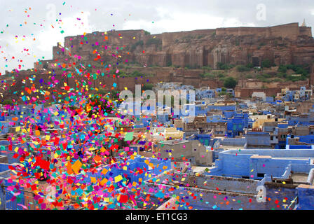 Mehrangarh fort and blue houses colourful pieces of papers flying ; Jodhpur ; Rajasthan ; India - Stock Photo