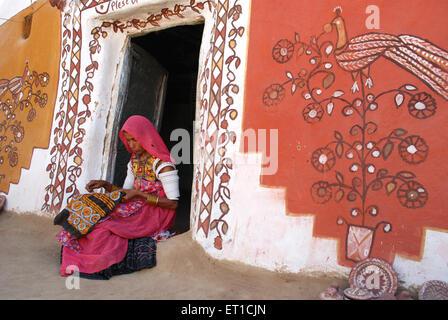 Indian woman doing embroidery work Khuri Jaisalmer Rajasthan India - Stock Photo