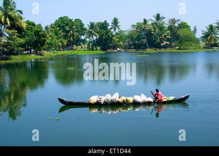 Man carrying big bags on boat in ashtamudi river ; Kollam ; Alleppey ; Kerala ; India - Stock Photo
