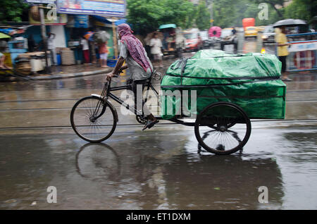 man riding tricycle with luggage on street in Kolkata at West Bengal India Asia - Stock Photo