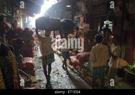 Man carrying vegetables sack in market Kolkata West Bengal India Asia - Stock Photo
