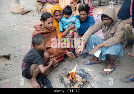 peoples warming hands over fire Kolkata West Bengal India Asia - Stock Photo