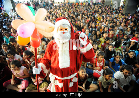 Santa claus coming around children ; Bombay Mumbai ; Maharashtra ; India NO MR - Stock Photo