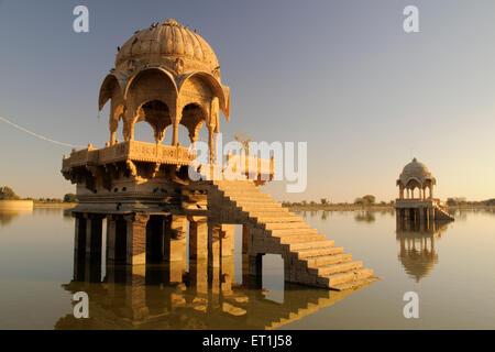 Two cenotaphs called chhatris reflections in water of Gadsisar or Gadisar lake ; Jaisalmer ; Rajasthan ; India - Stock Photo