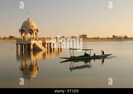 Cenotaph called chhatri reflection and boat known shikara in water of Gadsisar or Gadisar lake ; Jaisalmer ; Rajasthan - Stock Photo