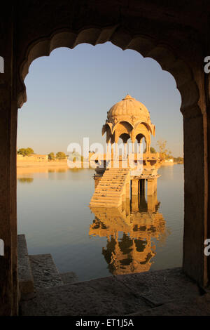 Cenotaph called chhatri reflection in water through arch in Gadsisar or Gadisar lake ; Jaisalmer ; Rajasthan ; India - Stock Photo