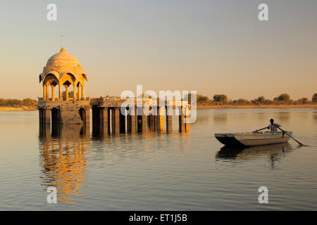 Cenotaph called chhatri and pillars reflection and rowing boat in waters of Gadsisar or Gadisar lake ; Jaisalmer - Stock Photo