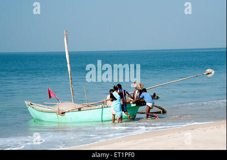 Fishermen and woman on khavne beach at sindhudurg ; Maharashtra ; India - Stock Photo