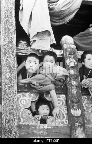 Young monks peep out a window in the monastery at Paro to look at dancers ; Bhutan - Stock Photo