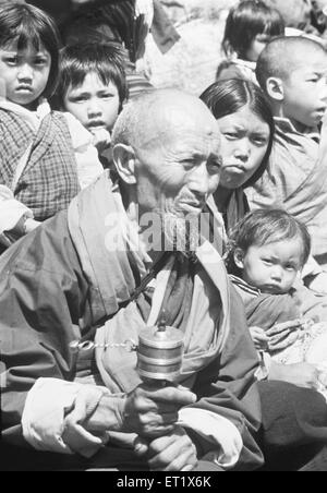 Old man dressed in traditional costume turns the prayer wheel at festival ; Bhutan - Stock Photo