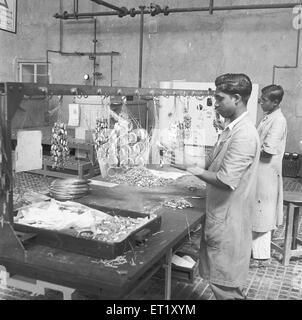 Workers at the assembly line ; telephone factory ; manufacturing of telephone instruments at Bangalore ; Karnataka - Stock Photo