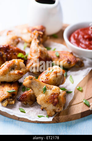 Fried chicken wings with sauces on wooden board, close up, selective focus - Stock Photo