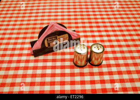 Steel salt and pepper dispensers and paper napkin holder on red and white checked tablecloth ; Goa ; India - Stock Photo