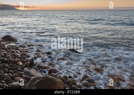 Gentle waves of Banderas Bay rolling over rocks and pebble at sunset - Stock Photo