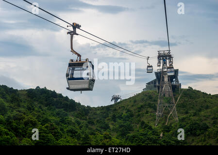 Cable cars rise up over the mountains of Lantau Island in Hong Kong, SAR. - Stock Photo