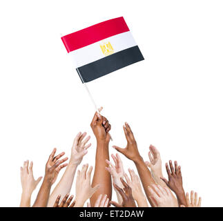 Group of multi-ethnic people reaching for and holding the flag of Egypt. - Stock Photo