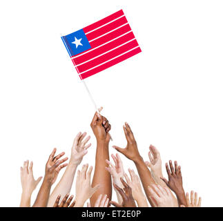 Group of multi-ethnic people reaching for and holding the flag of Liberia. - Stock Photo