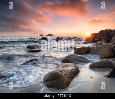 Sea rounded boulders at Porth Nanven beach in the far west of Cornwall - Stock Photo