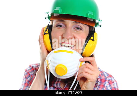 Smiling female construction worker with protective mask wearing green helmet and protective headphones, safety - Stock Photo