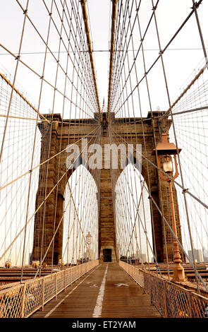 The Brooklyn Bridge spanning the East River from Manhattan to Brooklyn. The Bridge is a hybrid cable-stayed suspension - Stock Photo
