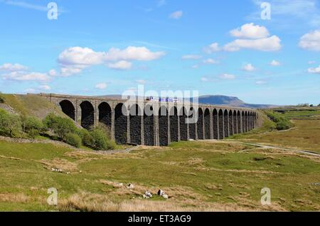 Diesel multiple unit train on Ribblehead Viaduct on the Settle to Carlisle railway line with Pen-y-Ghent in the - Stock Photo