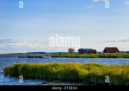 Seaside idyll in the evening light with huts and boats on the island of Oland, Sweden. - Stock Photo