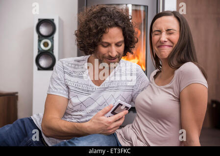 Mid adult man showing mobile phone to his wife, Munich, Bavaria, Germany - Stock Photo