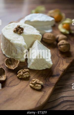 Close-up of cheese and walnuts on chopping board, Germany - Stock Photo