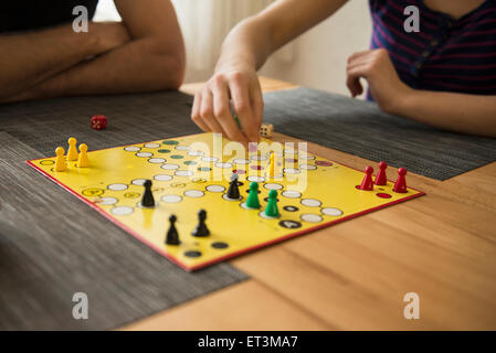 Mid section of father and daughter playing a board game, Bavaria,  Germany - Stock Photo