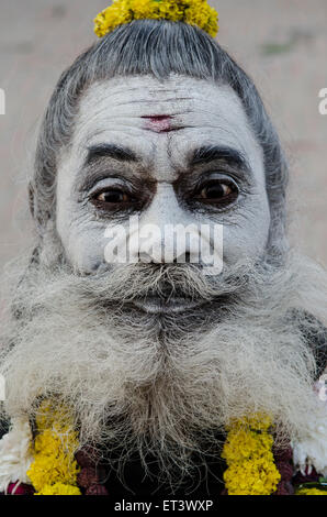A sadhu poses for a photograph on the banks of the Ganges - Stock Photo