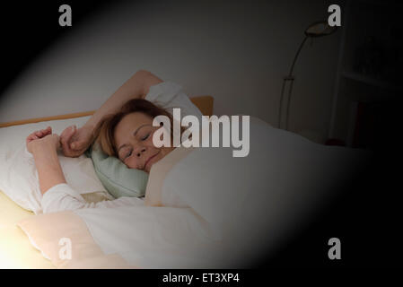 Senior woman sleeping on bed in bedroom, Munich, Bavaria, Germany - Stock Photo