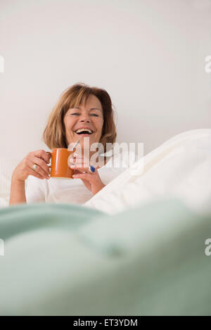 Senior woman at her bedroom drinking tea in the morning, Munich, Bavaria, Germany - Stock Photo