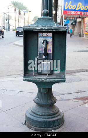 Old Pay phone on a street corner in the French Quarter of New Orleans Louisiana - Stock Photo