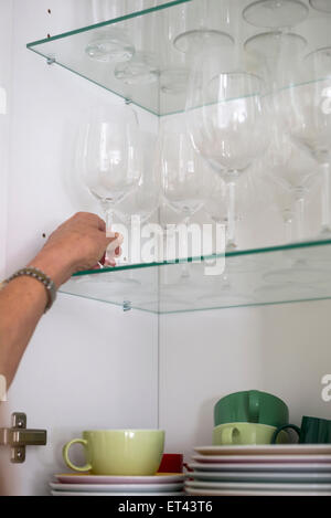 Close-up of a woman taking wineglass from cupboard, Munich, Bavaria, Germany - Stock Photo