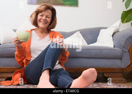 Happy senior woman having cup of tea with and sitting on floor at home, Munich, Bavaria, Germany - Stock Photo