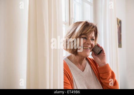 Happy senior woman talking on cell phone at home, Munich, Bavaria, Germany