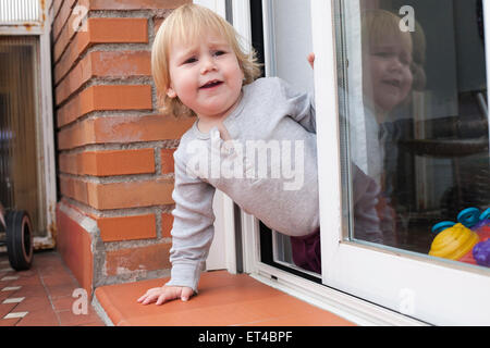 portrait of blonde caucasian baby nineteen month age chubby face calling peering terrace floor supported on the - Stock Photo