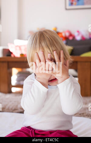 portrait of blonde caucasian baby nineteen month age covering her face with two hands white shirt - Stock Photo