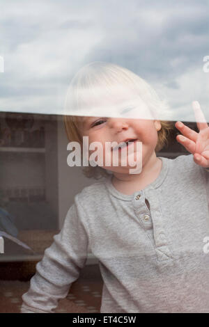 portrait of smiling blonde caucasian baby nineteen month age chubby face looking at camera through reflecting glass - Stock Photo