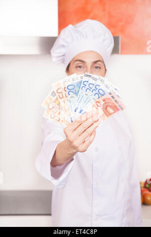 wad of fifty twenty and ten Euro banknotes wad in hands of brunette happy chef woman with professional jacket and - Stock Photo