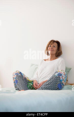 Senior woman sitting on bed and thinking, Munich, Bavaria, Germany - Stock Photo