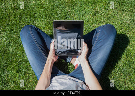 woman blue jeans trousers grey shirt legged with digital tablet blank screen in her hands sitting on green grass - Stock Photo