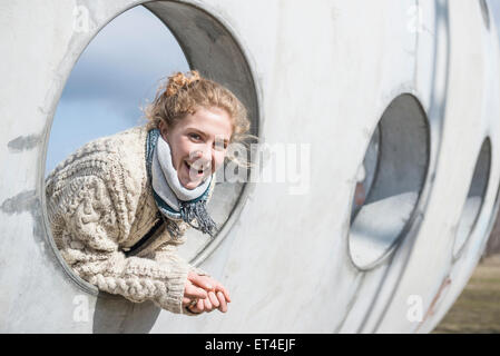 Young woman looking through a round hole in concrete wall Munich Bavaria Germany - Stock Photo