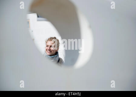 Young woman seen through a round hole in concrete wall Munich Bavaria Germany - Stock Photo
