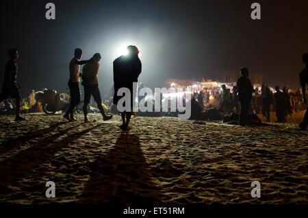 A worshiper crosses the beach at Maga Sapthami sun festival in Konark, Odisha, India - Stock Photo