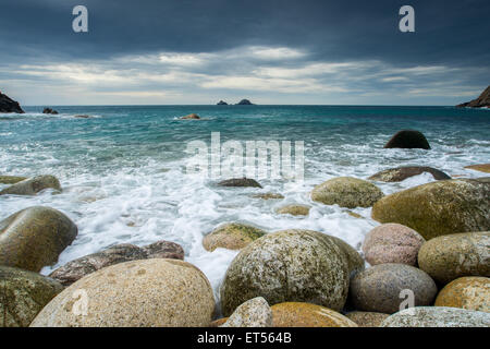 Boulder covered beach at Porth Nanven at the end of Cot Valley with the Brisons on the Horizon, Cornwall England - Stock Photo