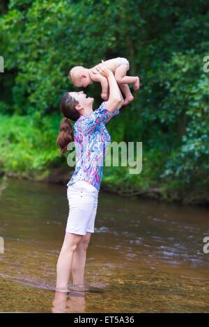 Young beautiful mother playing with her little baby hugging and kissing him enjoying a hot summer day in a little - Stock Photo
